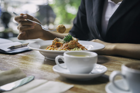 Fokus auf Frau isst Spaghetti mit Tasse Tee