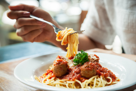 italienisches essen: Nahaufnahme von Frau isst Spaghetti mit Gabel