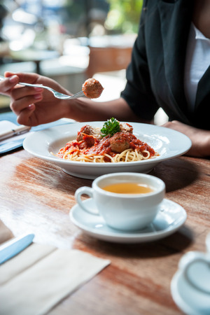 spicy food: portrait image of woman eating spaghetti meatball