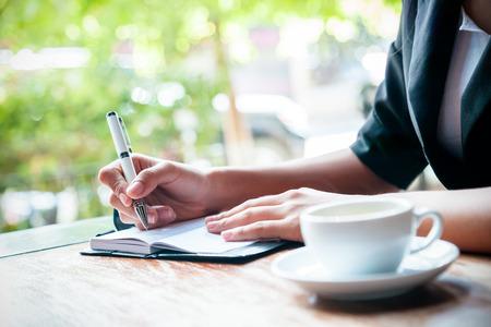 boligrafos: close up de la revista Mujer escrito y taza de café Foto de archivo