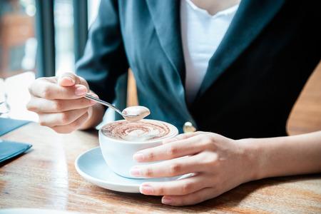stirring: close up of woman stirring her coffee
