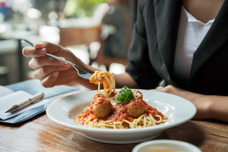 noodle: focus on woman eating spaghetti with journal Stock Photo