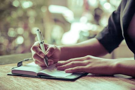 un gros plan de femme écrit son journal