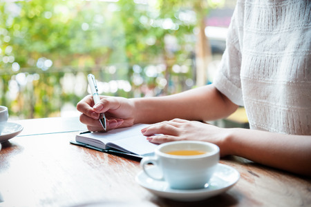 cup of tea with background of woman writing