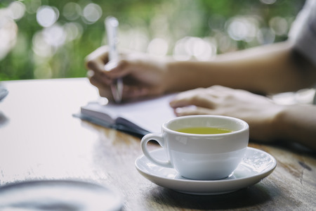 cup of tea with background of woman writing Stock Photo - 43281104