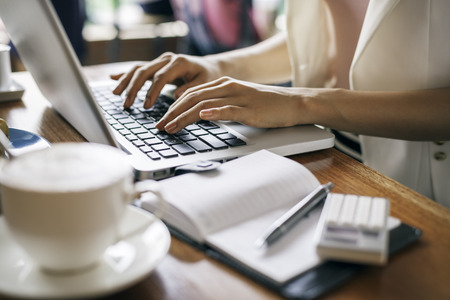 woman typing: journalist typing document in a coffee shop