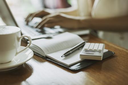 calculadora: autor escribiendo trabajar en el interior de una tienda de café Foto de archivo