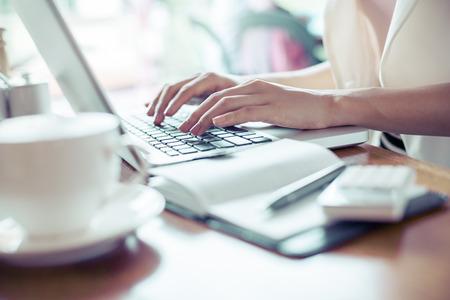 calculadora: Mujer escribiendo documento sobre el portátil en café Foto de archivo