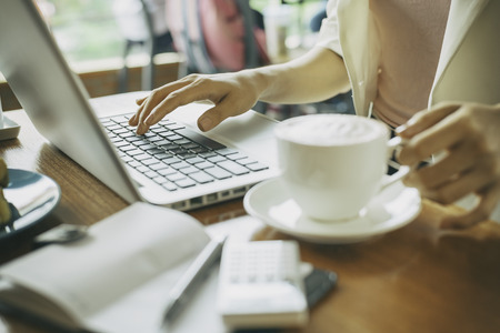 hands at work: woman holding cup of coffee while working Stock Photo