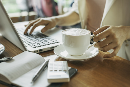 journal: woman holding cup of coffee while working Stock Photo