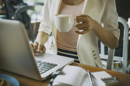 woman working: woman working on laptop while holding coffee Stock Photo