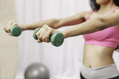 Weights: woman lifting small weights with both hands Stock Photo