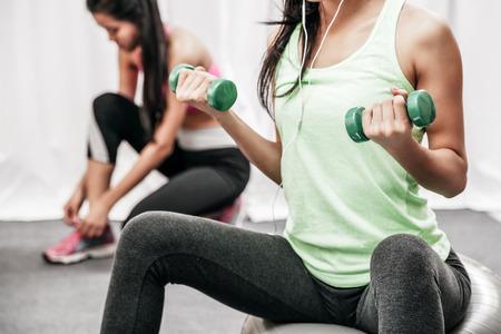 close-up van de vrouw lift gewicht, terwijl zittend op gigantische bal en een andere vrouw koppelverkoop schoen Stockfoto