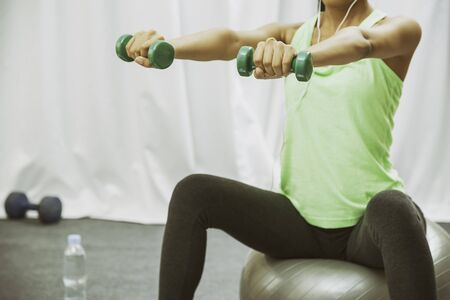 Weights: close up of woman lift weight while sitting on giant ball Stock Photo
