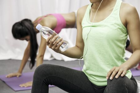 close up of woman holding water bottle while sitting down relaxing and another woman doing push up