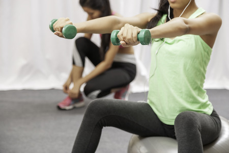 Weights: close up of woman lift weight while sitting on giant ball and another woman tying shoe Stock Photo