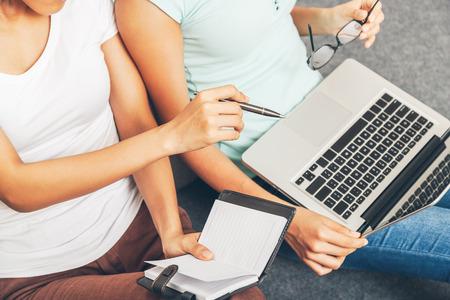 persona escribiendo: dos estudiantes universitarios que se�alan y que discuten en su computadora port�til Foto de archivo