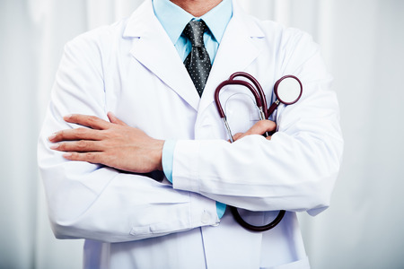 close up of a doctor folding arms and holding a stethoscope