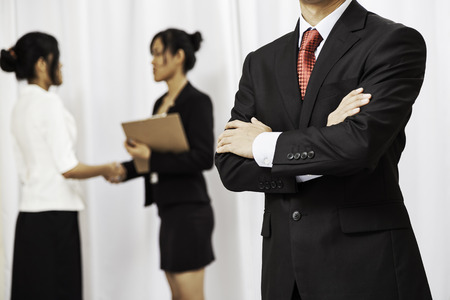 folding arms: businessman stand folding his arms while two women shake hands in the background
