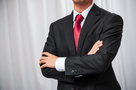 folding arms: businessman in a tuxedo standing and folding his arms Stock Photo