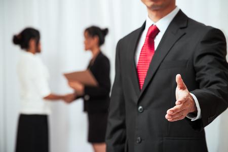 traje formal: negocios la celebraci�n de su mano para apret�n de manos, mientras que dos mujeres se dan la mano en el fondo Foto de archivo