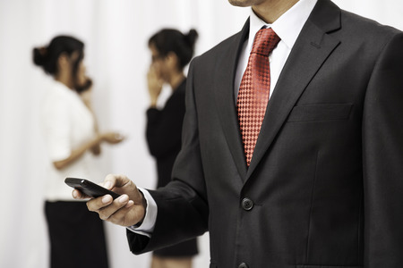 businessman phone: businessman using his mobile phone while two women are talking in the background