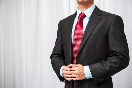 black professional: confident businessman standing formally holding his tuxedo