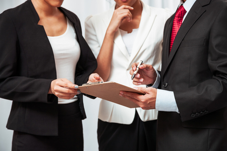 black businessman: three business people standing and discussing their work