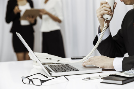 executive assistants: inside the executive office, the boss talking on the phone and assistants discussing work
