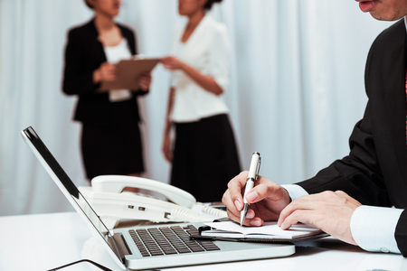executive assistants: inside the executive office with the boss working and assistants discussing work Stock Photo