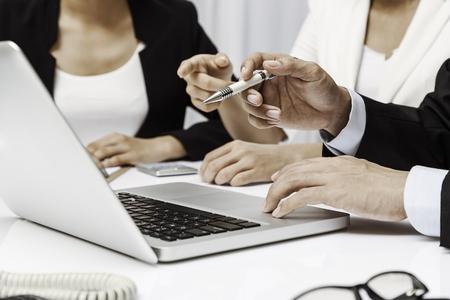 drie mensen uit het bedrijfsleven bespreken hun werk op een laptop
