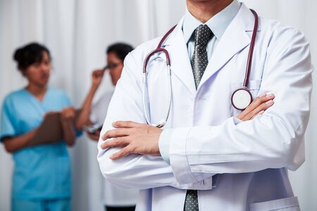 medical doctor stand folding his arms while nurses standing in the background