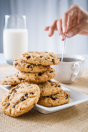 close up of cookie and hand stirring cup of teacoffee
