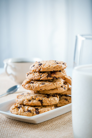 tea table: cookies stacked on each other on plate, glass of milk and cup of teacoffee Stock Photo