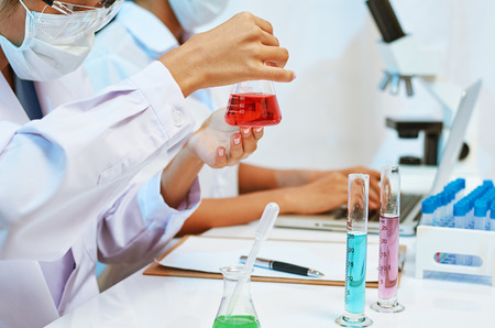 experimenting: two scientists experimenting and analysing with chemicals in laboratory Stock Photo