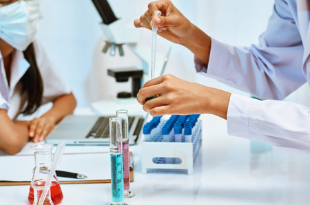 experimenting: two scientists experimenting with chemicals in laboratory Stock Photo
