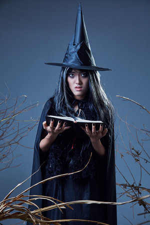 woman in witch costume holding a spell book Stock Photo