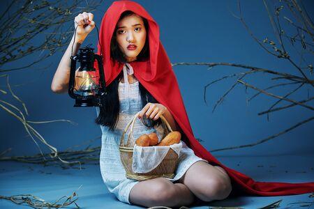 caperucita roja: la pequeña sentada caperucita roja que sostiene una linterna y una cesta de pan Foto de archivo