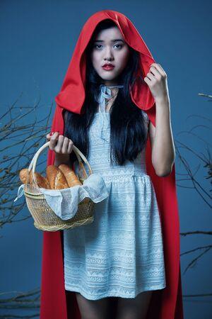 caperucita roja: la caperucita roja que se coloca con su cesta de pan Foto de archivo