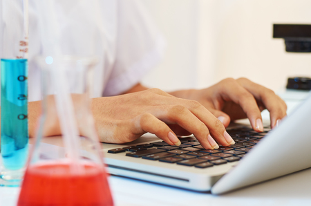 physicists: scientist typing documents into laptop in the laboratory Stock Photo