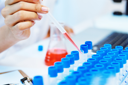 close up of scientists experimenting and testing chemicals in laboratory