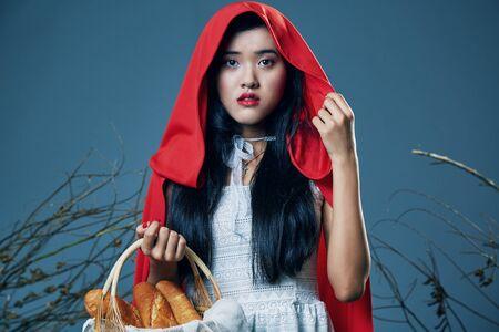 little red riding hood: la caperucita roja que se coloca con su cesta de pan Foto de archivo