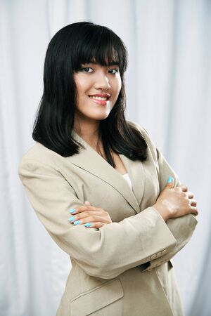 folding arms: happy businesswoman wearing beige suit standing and folding arms