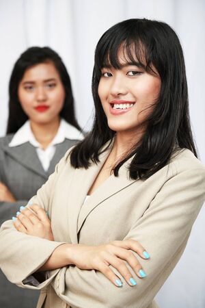 folding arms: happy businesswomen wearing suits standing and folding arms Stock Photo