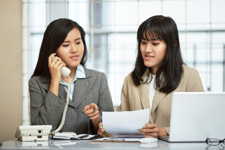 telephoning: close up image of two businesswomen working and discussing in office Stock Photo