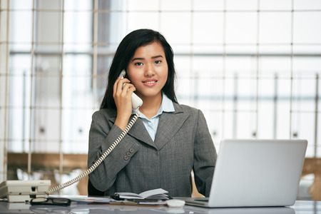 front desk: friendly smile of front desk businesswoman telephoning the client