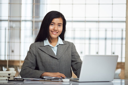 front desk: friendly smile of front desk businesswoman sitting in front of her computer Stock Photo