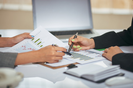 collaborating: close up image of businesswomen discussing and consulting document