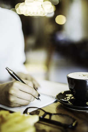 portrait image of a woman writing her notebook in a cafe Stock Photo