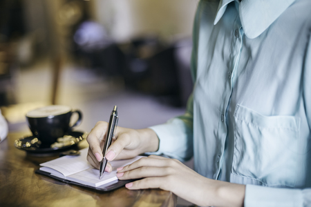 school cafeteria: woman in blue blouse writing in her notebook Stock Photo